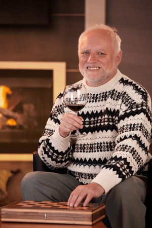Portrait of happy senior man having wine at home in front of fireplace, hand on chess set, smiling at camera. Stock Photo - 8250953