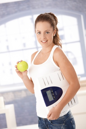 Pretty girl holding scale and apple in hands, smiling, dieting. Stock Photo - 8251168