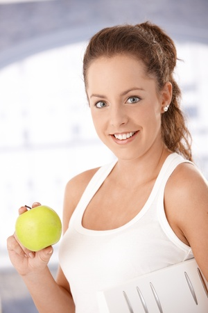 Portrait of pretty girl holding an apple in hand, smiling front of window, dieting. Stock Photo - 8251123