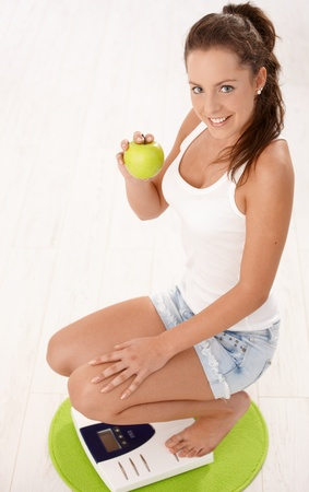 Young attractive female squatting on scale, holding an apple in hand, smiling, dieting. Stock Photo - 8250961