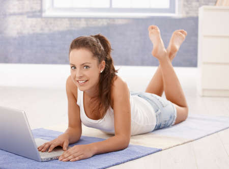 Attractive young female using laptop, downloading e-mails, laying on floor at home, smiling. photo