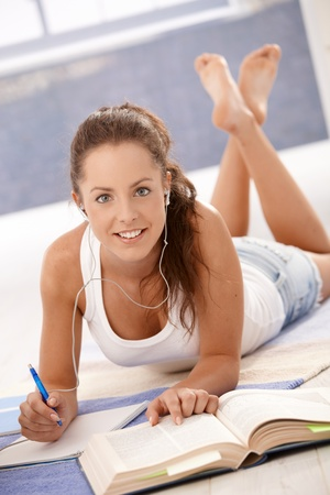 Attractive young female studying at home, laying on floor, smiling. photo