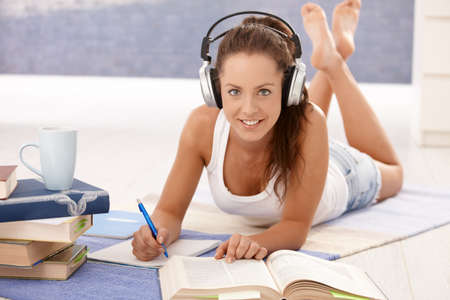 Pretty girl learning at home laying on floor, using headphones, smiling. photo