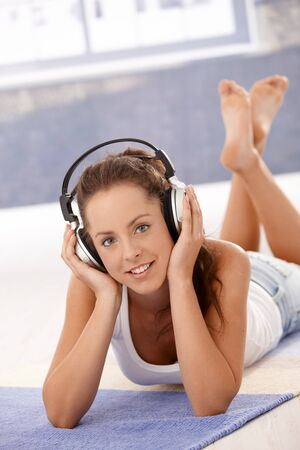 Attractive young female girl listening to music, using headphones, laying on floor at home, smiling. Stock Photo - 8251239