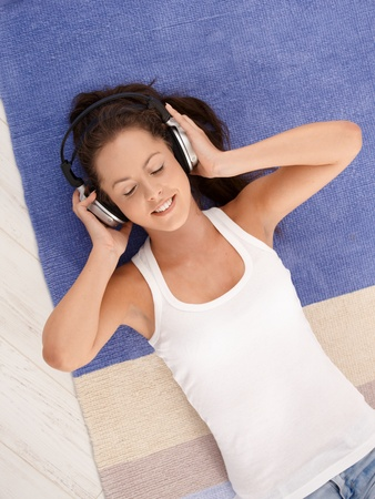 Attractive girl laying on floor at home, listening to music through headphones, smiling, eyes closed. Stock Photo - 8251349