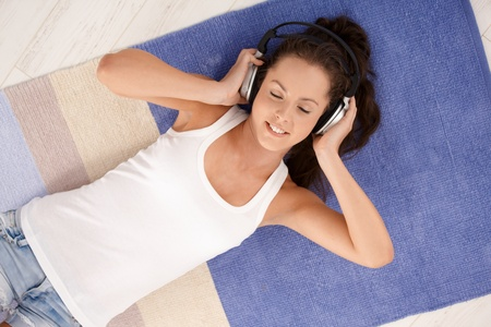 Attractive young female laying on floor at home, listening to music through headphones, smiling, eyes closed. Stock Photo - 8251354