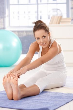 haciendo ejercicio: Atractiva joven haciendo ejercicios sobre el piso en el hogar, sonriendo.  Foto de archivo