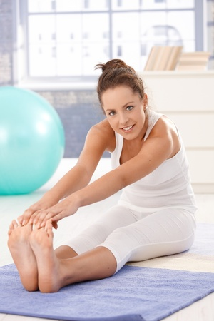 recreation room: Attractive young woman doing exercises on floor at home, smiling.