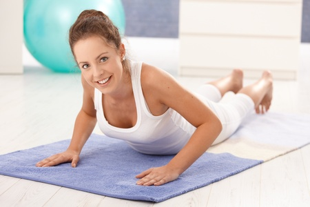 Pretty young girl doing exercises on floor at home, smiling. photo