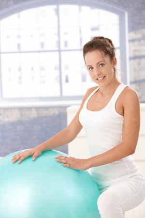 Pretty young girl exercising with fitball at home, smiling. photo