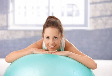 Attractive female leaning on fitball after workout, taking a break, smiling in gym. photo