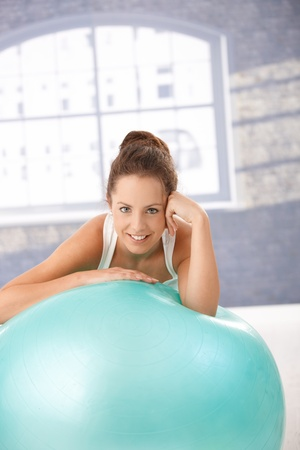 Pretty girl resting on fitball after workout, smiling in gym. photo