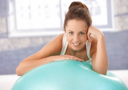 Pretty girl resting on fitball after doing gymnastics, smiling in gym. Stock Photo - 8251008