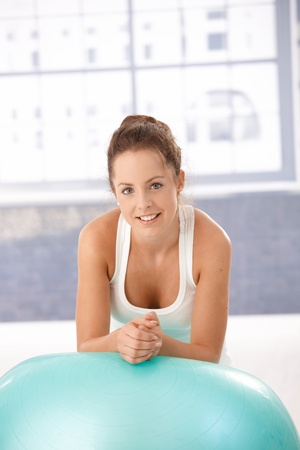 Attractive young woman resting on fitball after workout, smiling in gym. photo