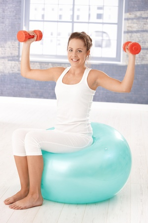 Pretty girl exercising with dumbbells on fitball, smiling in gym. Stock Photo - 8251015