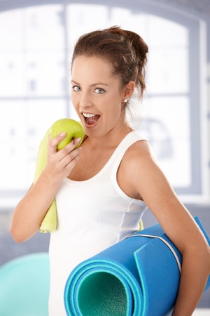 Pretty girl biting an apple after exercising in gym. photo