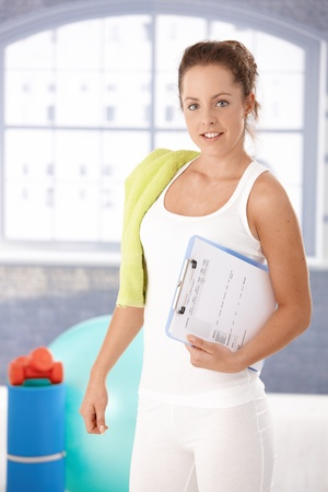 Pretty young girl prepared for personal training in gym, holding her training plan in hand. photo