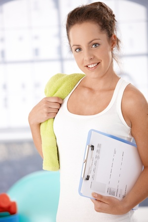look after: Pretty young girl prepared for personal training in gym, holding her training plan in hand. Stock Photo