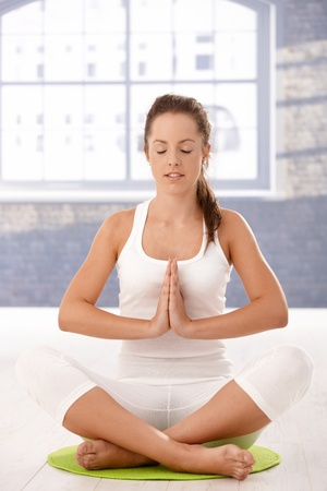 Young attractive woman practicing yoga, meditating in prayer pose in studio. Stock Photo - 8251065