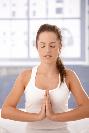 Young attractive woman practicing yoga, meditating in prayer pose in studio.