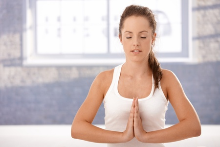 Pretty young girl practicing yoga, meditating in prayer pose in studio, eyes closed. photo