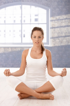 Pretty girl practicing yoga in studio, sitting on floor, relaxing. photo