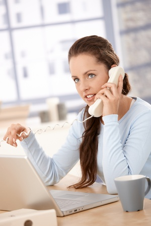 Attractive young girl working on laptop in bright office, talking on phone. photo
