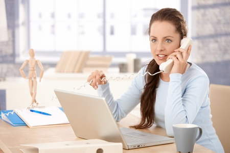 Attractive young femalel working on laptop in bright office, talking on phone. Stock Photo - 8251054