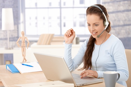 headset woman: Young attractive customer servicer talking on headphones, using laptop, smiling.