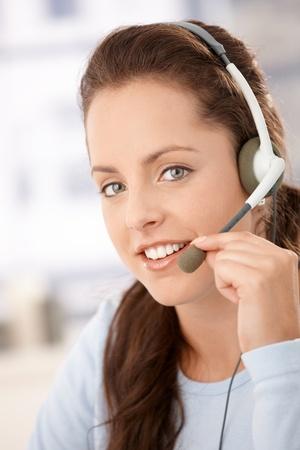 Portrait of pretty dispather talking on headphones, smiling. photo