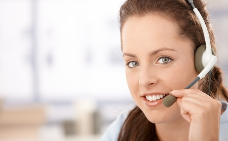 Portrait of pretty dispather talking on headphones, smiling. Stock Photo - 8250962