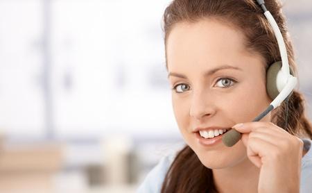 Portrait of pretty dispather talking on headphones, smiling. Stock Photo - 8250962