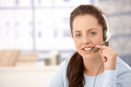 Portrait of young, attractive dispather talking on headphones, smiling. Stock Photo - 8251017