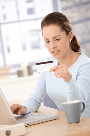 Young woman using laptop, shopping on internet, using credit card. photo