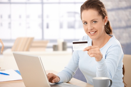 Young woman using laptop, shopping on internet, using credit card, smiling. photo