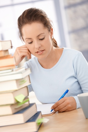 textbooks: Attractive college student preparing for exam, sitting at table.
