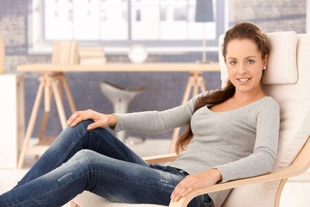 Pretty young girl relaxing at home in armchair, smiling. photo