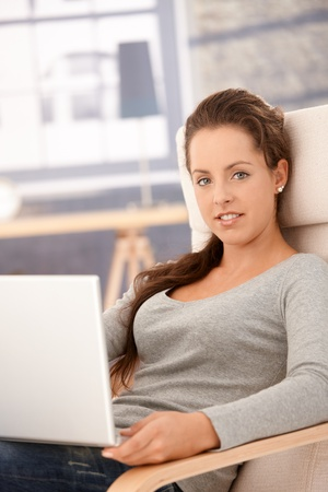 Attractive young female browsing internet on laptop, sitting in armchair at home, smiling. photo
