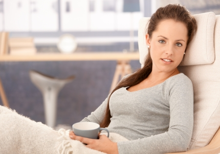 eyes closed: Young attractive girl relaxing in armchair at home, drinking tea.