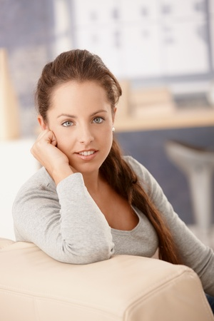 Portrait of pretty girl sitting on sofa at home, smiling. Stock Photo - 8251119