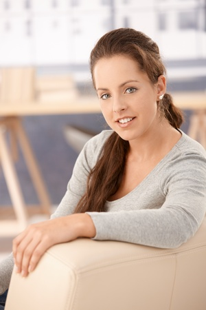 Portrait of pretty girl sitting on sofa at home, smiling. Stock Photo - 8251196