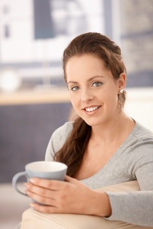 Attractive woman sitting on sofa at home, drinking tea, smiling. Stock Photo - 8251238