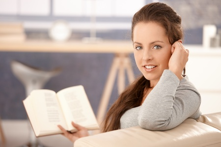 Young attractive girl reading book at home, sitting on sofa, smiling. photo