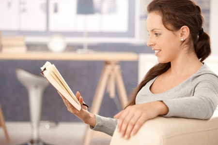 Young woman reading book at home, sitting on sofa, smiling. photo