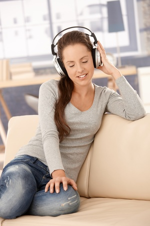 Young woman listening to music at home, sitting on sofa, smiling, using headphones, eyes closed. Stock Photo - 8251343