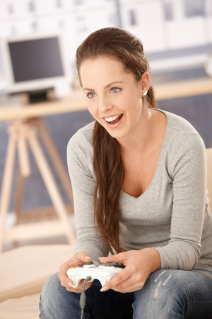 Attractive young girl playing computer game at home, having fun, laughing. Stock Photo - 8251294