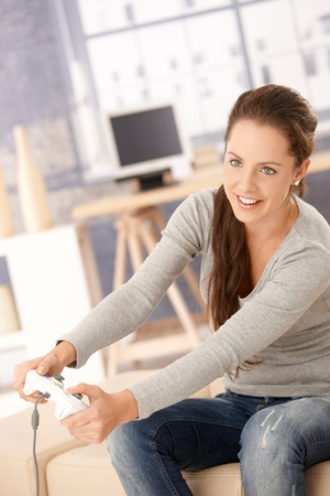 Attractive young woman playing computer game at home, having fun, laughing. Stock Photo - 8251293