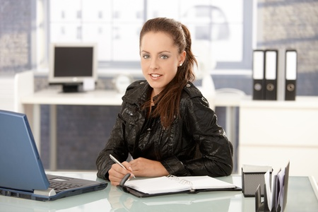 clothes organizer: Young attractive woman working in bright office, using laptop, smiling.