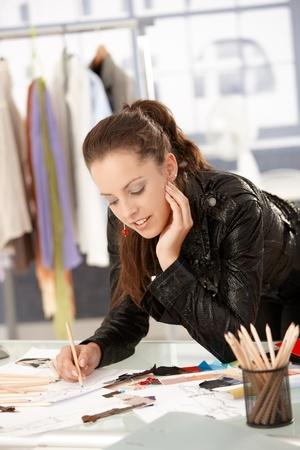 Atractivo diseñador de modas trabajan en la Oficina, apoyándose en el escritorio, dibujo.