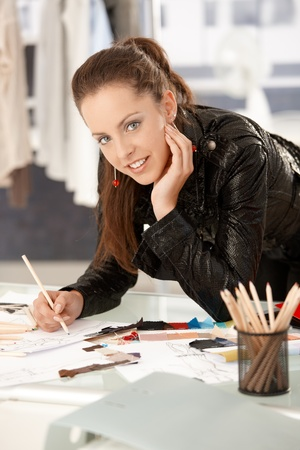 designed: Pretty, young fashion designer working in office, leaning on desk, drawing. Stock Photo